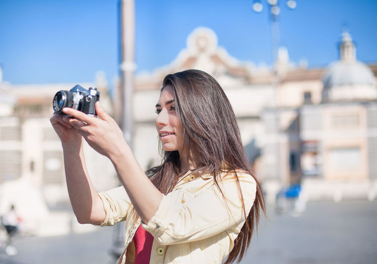 Young woman tourist in the city Brunette Camera City Day Italy Leisure Activity Lifestyles Outdoors Photo Pretty Red Rome Summer Tourism Tourist Urban Woman Young