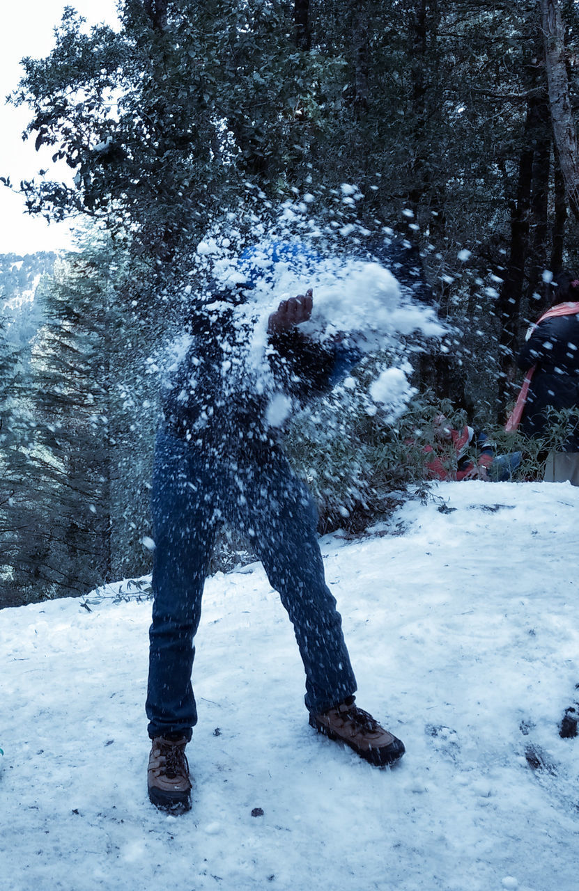 snow, winter, cold temperature, tree, plant, nature, day, land, field, one person, lifestyles, real people, standing, warm clothing, motion, leisure activity, men, covering, outdoors, snowing