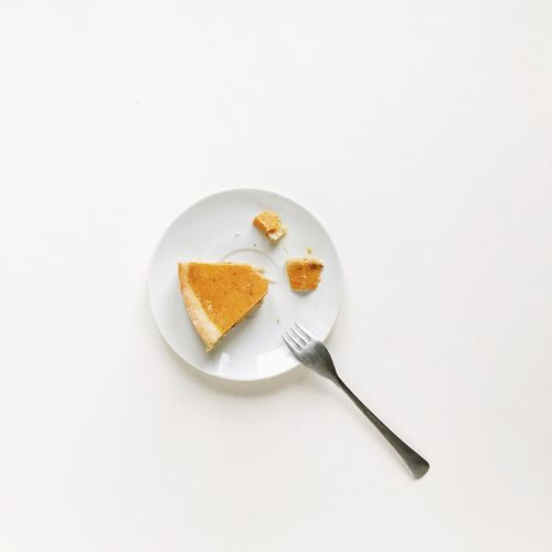 top view of a pumpkin pie in a dressing of decorative pumpkins by Thanksgiving Day Food Food And Drink Kitchen Utensil Eating Utensil Fork Indoors  White Background White Color Spoon High Angle View No People Sweet Food Directly Above Freshness Studio Shot Ready-to-eat Indulgence Plate Still Life Copy Space