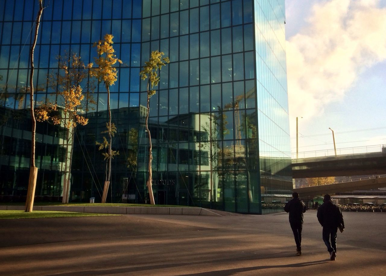 People Walking Past Glass Building