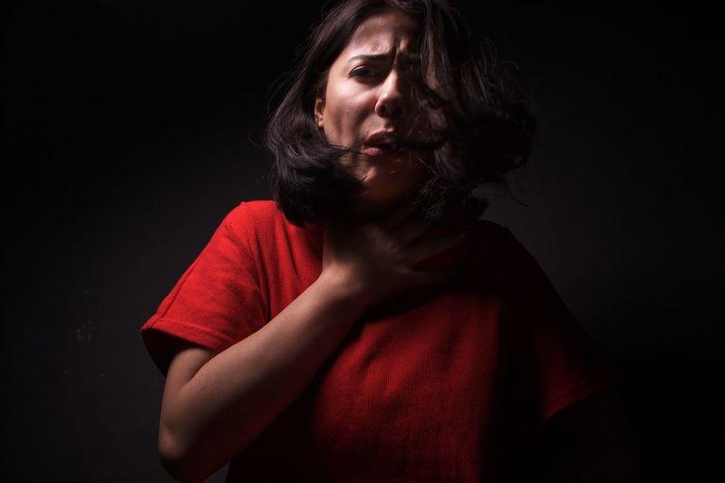Portrait Of Woman With Neckache Against Black Background