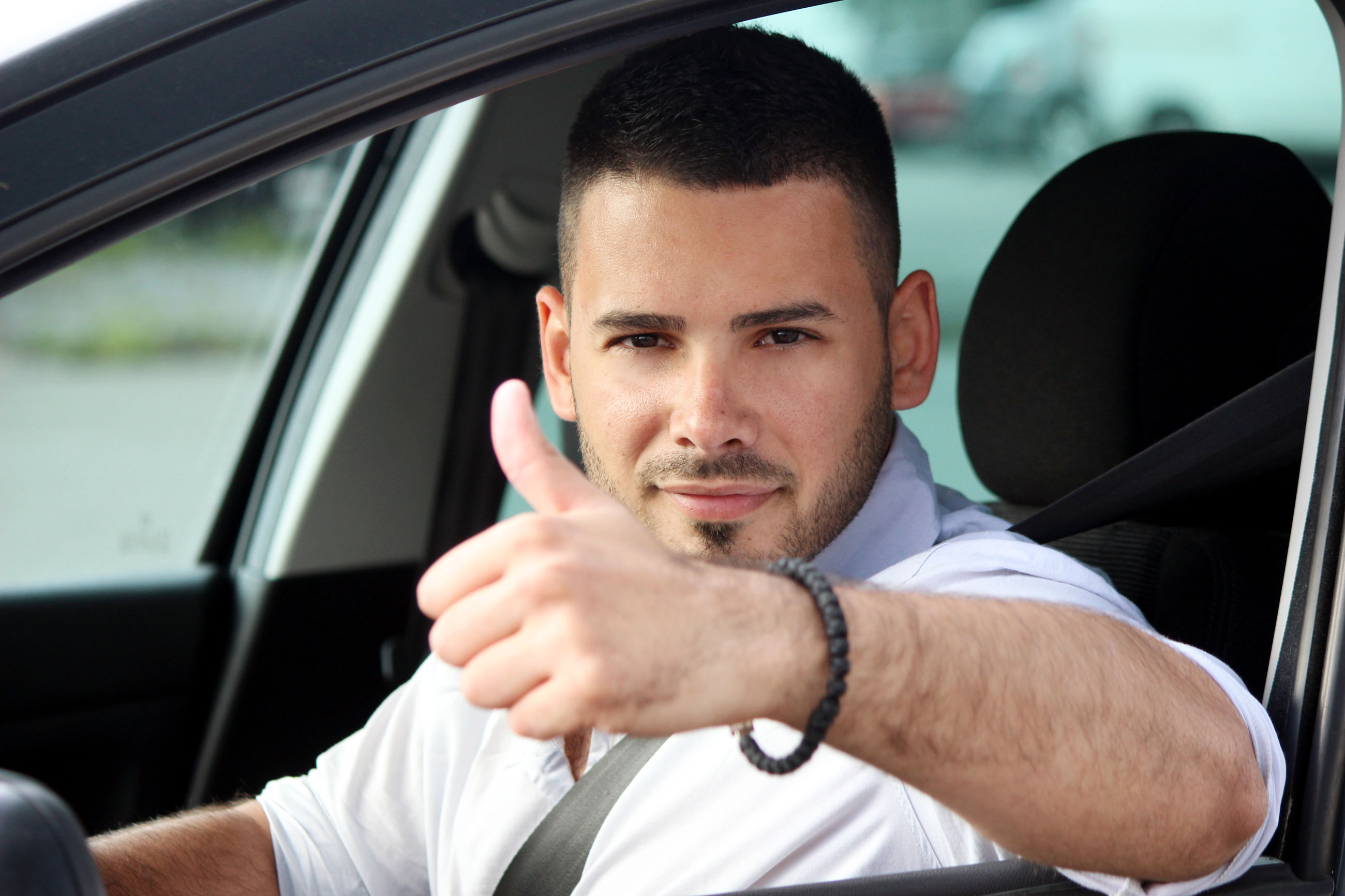 PORTRAIT OF YOUNG MAN SITTING WITH CAR