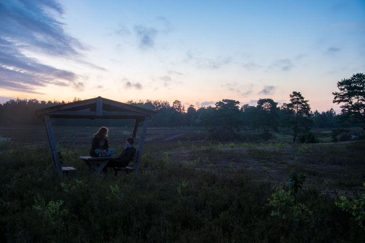 Young couple sitting at gazebo on field against sky during sunset
