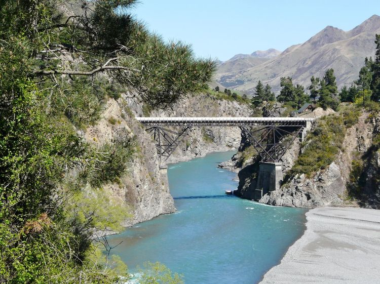 One Way Bridge spanning Turquiose Waters Beauty In Nature Blue Bridge Built Structure Day Glacial Water Green Color Hanmer Springs Hill Landscape Mountain Mountain Range Nature New Zealand Scenery No People Non-urban Scene Outdoors Plant Scenics Sky Tranquil Scene Tranquility Travel Destinations Tree Turquoise