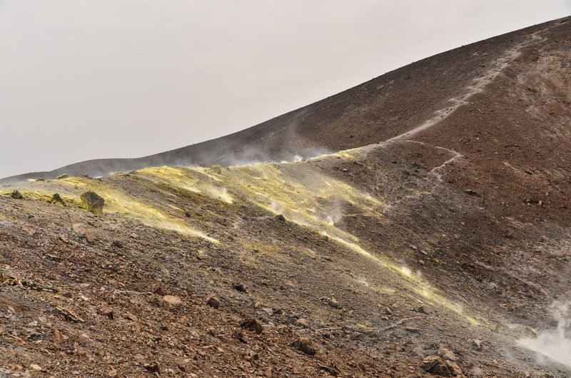 Sulphur Gas On Arid Landscape Against Clear Sky