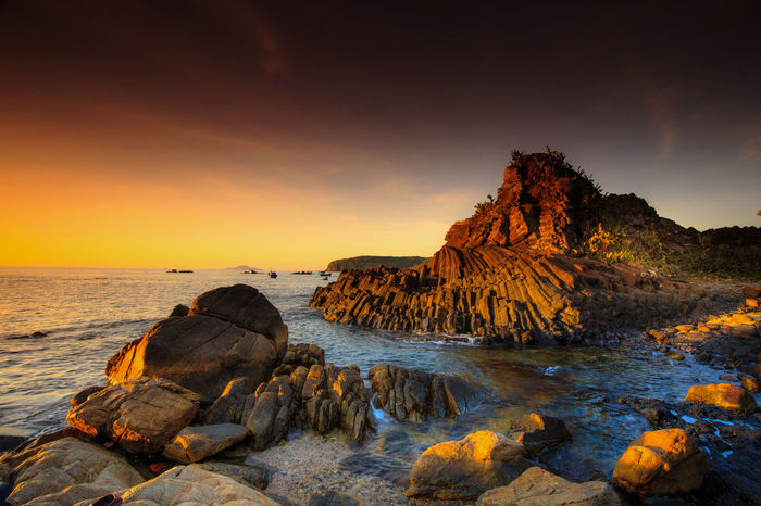 Sunset on rocky coast in Phu Yen, Vietnam Peaceful Tourism Basalt Basket Boat Cliff Cloud Coastal Dusk Geological Geology Hexagonal Landscape Morning Ocean Pannier Phuyen Polygonal Reef Seashore Stone Sunrise Travel Tropical Wallpaper Wave