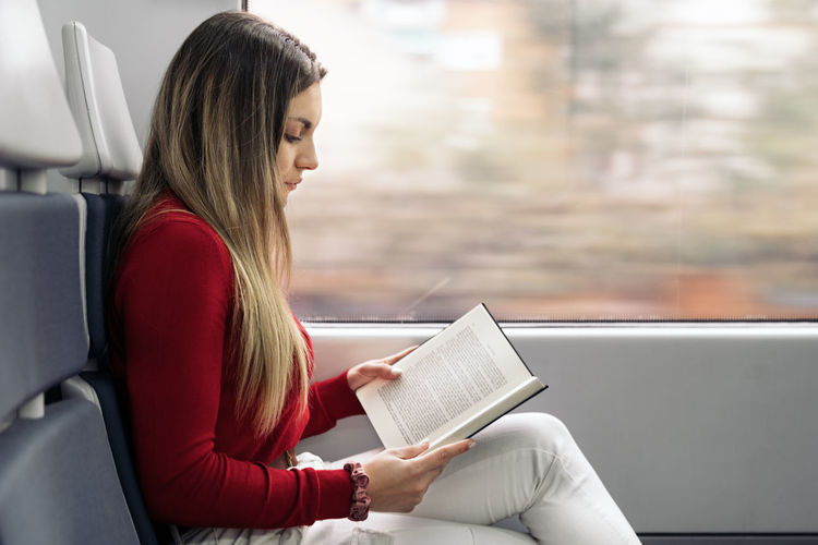 Woman holding book while sitting on seat