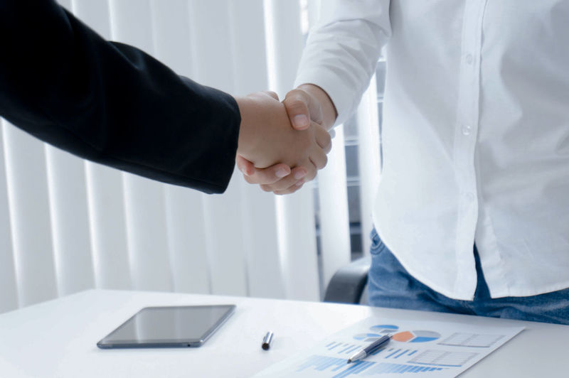 business mans handshake. Business partnership meeting successful concept Adult Agree Agreement Background Business Businessman Businesswoman Close Commerce Communication Company Concept Contract Cooperation Corporate Deal Friendship Greeting Group Hand Handshake Happy Human Job Male Meeting Men Office Partner Partnership People person Power Professional Shake Staff Success Successful Suit SUPPORT Team Teamwork Together Trade Trust Two Union White Work Worker Two People Indoors  Midsection Males  Well-dressed Occupation Business Person Table Partnership - Teamwork Coworker