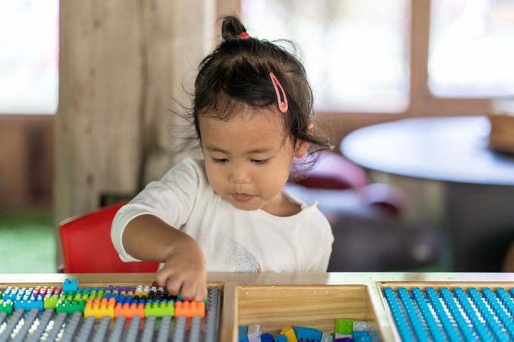 Cute girl playing with toy blocks on table at home