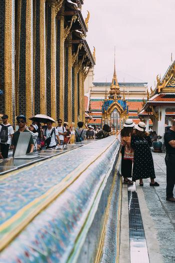 People walking outside temple against buildings