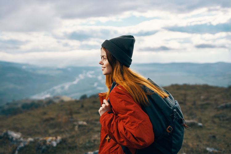Side view of young woman looking at mountain against sky