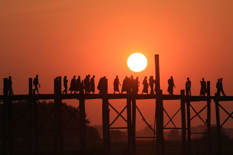 Silhouette monks and people on u bein bridge over river during sunset
