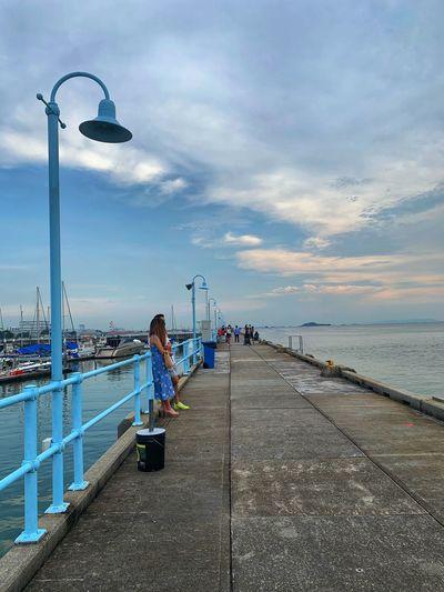Man on pier by sea against sky
