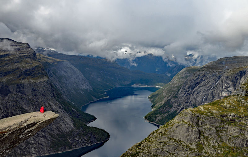 Sitting on Trolltunga Norway Activity Adventure Beauty In Nature Cloud - Sky Day Leisure Activity Looking At View Mountain Mountain Range Nature Non-urban Scene One Person Outdoors Real People Rock Scenics - Nature Sky Snowcapped Mountain Tranquil Scene Tranquility Trolltunga Norway Hiking Water