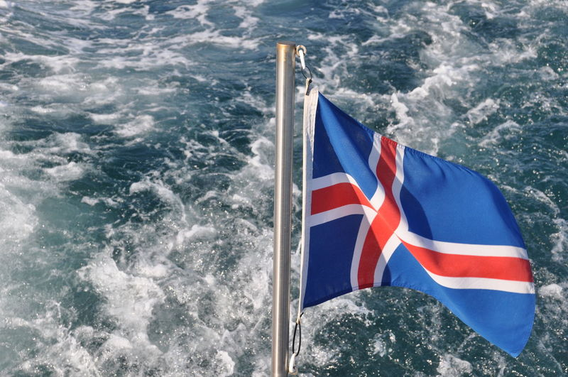 Close-up of flag against blue water