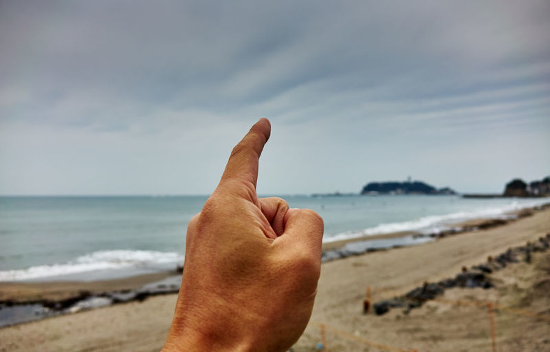 Cropped hand of man pointing at sea against sky
