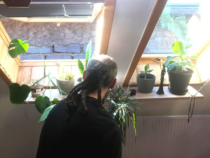 Rear view of women standing on potted plant at home