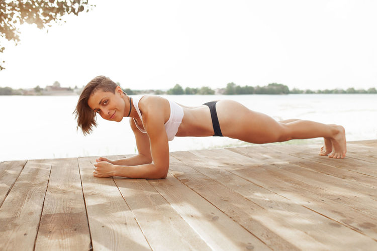 Beautiful woman with fit sport body do yoga exercises on the lake beach Beautiful Woman Day Exercising Fit Woman Flooring Full Length Hairstyle Healthy Lifestyle Leisure Activity Lifestyles Looking At Camera Nature One Person Outdoors Plank Planking Portrait Real People Relaxation Sky Women Wood Wood - Material Young Adult Young Women
