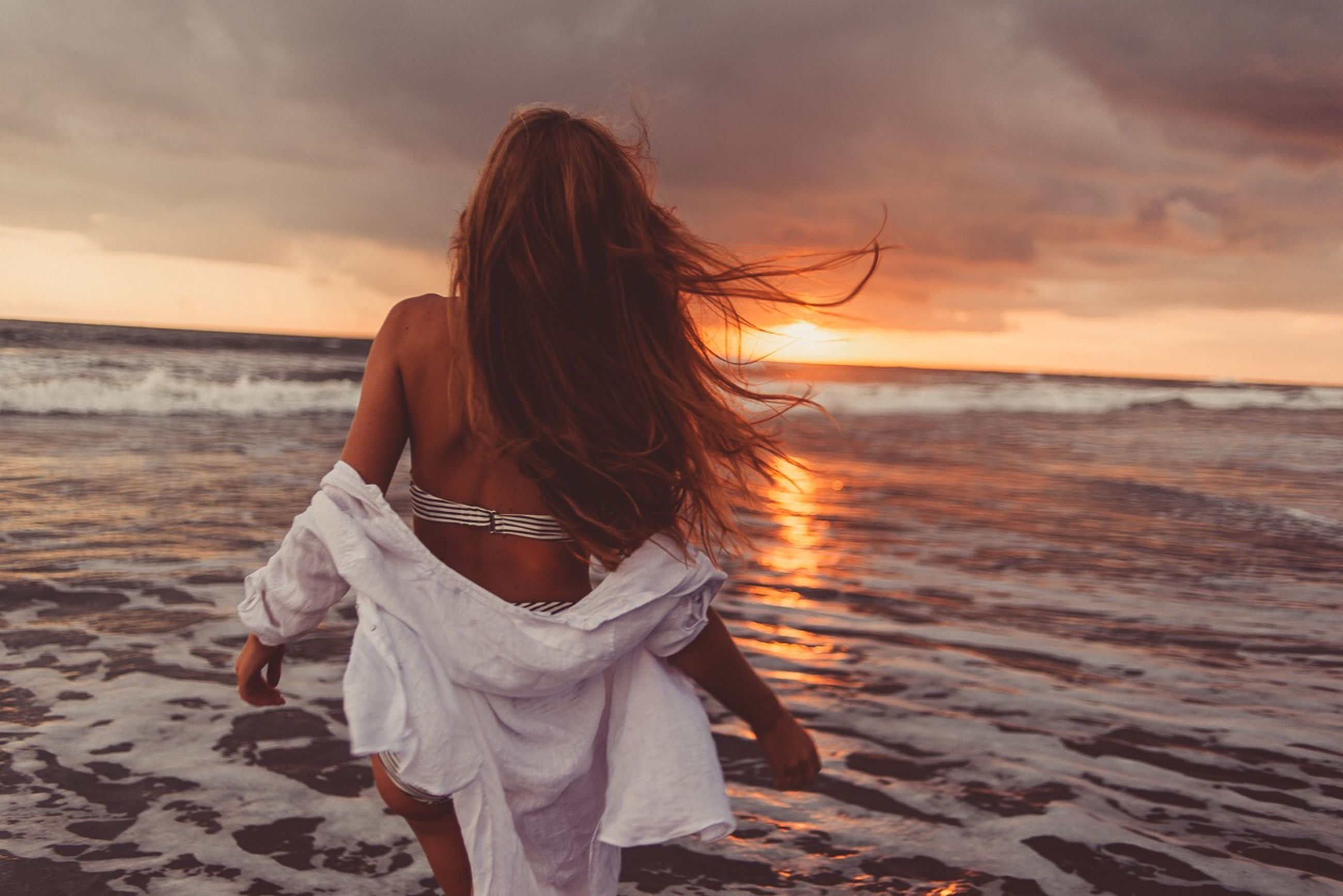 beach, sea, land, sky, sunset, water, one person, real people, beauty in nature, cloud - sky, women, leisure activity, hairstyle, scenics - nature, hair, lifestyles, rear view, nature, long hair, horizon over water, outdoors, looking at view, wind