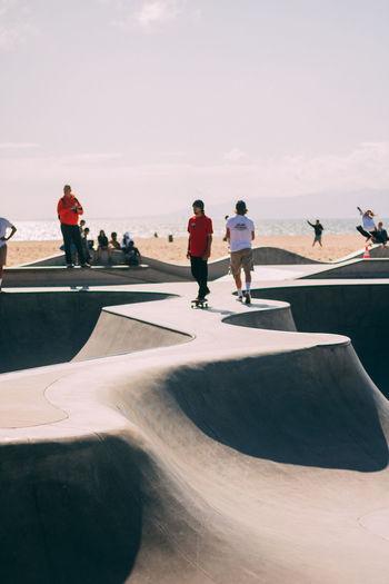 People on skateboard by sea against sky
