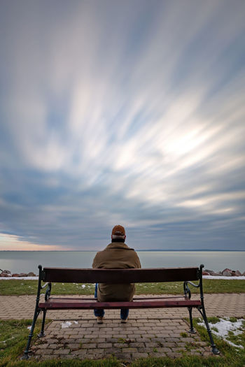 Rear view of man sitting on bench against sky