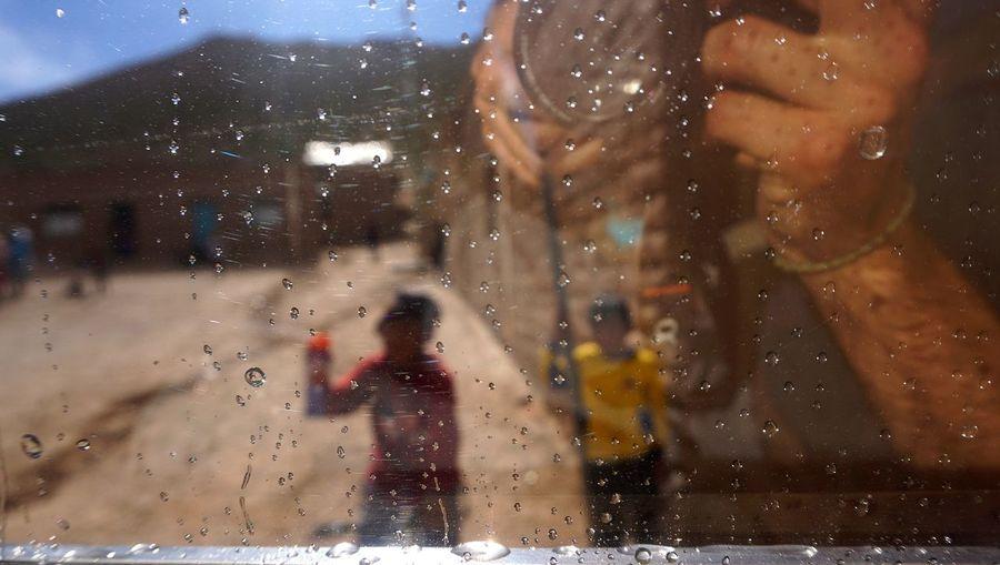 Woman walking on wet glass window in rainy season