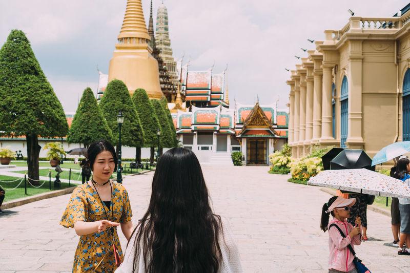 Portrait of friends outside temple against buildings