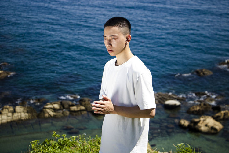 Young man standing in sea