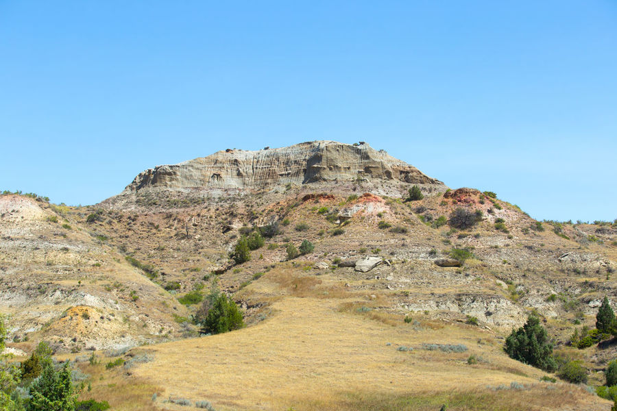 Beauty In Nature Blue Clear Sky Cliff Day Landscape Low Angle View Mountain Nature No People Outdoors Scenics Sky Theodore Roosevelt National Park Tranquil Scene Tranquility Tree