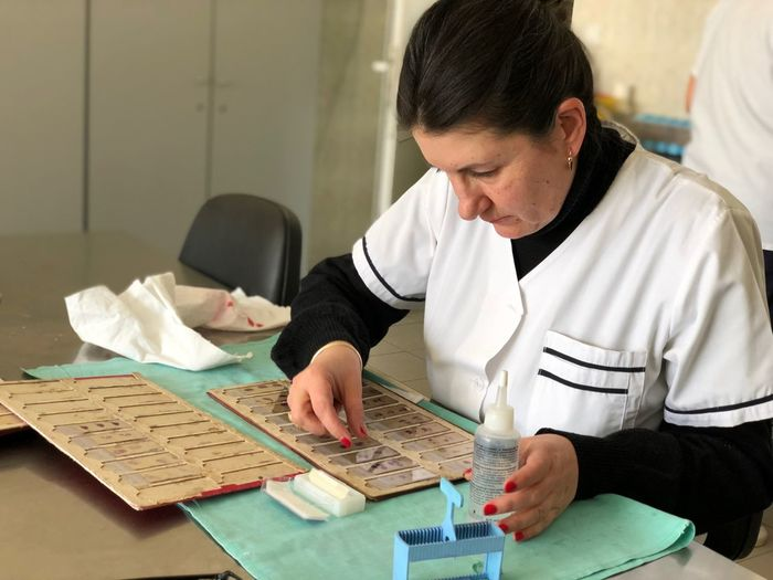 Female Scientist Examining Microscope Slide At Laboratory
