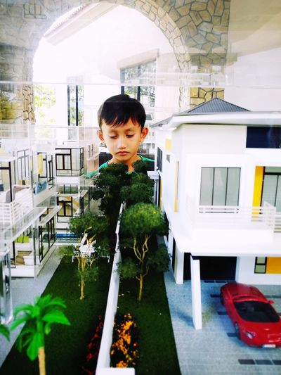 a young boy is interested with the housing mini modelling that is on display. Indoors  One Person Business Finance And Industry People Child One Man Only Portrait Young Adult Day Child Miniature Model Figure House Model Interest Learning Architecture Developer Johor Johor Bahru Johor Premium Outlet Creative Boy Little