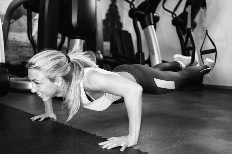 Smiling Woman Exercising At Gym