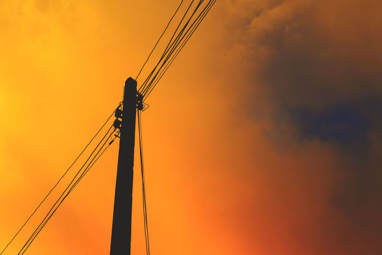 Low angle view of electric pole against orange sky