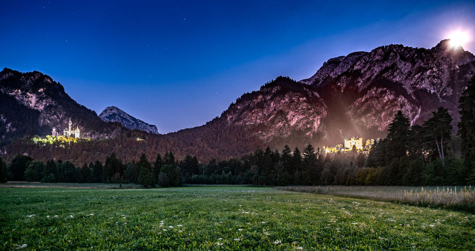 Scenic view of illuminated castles on mountains against sky at night