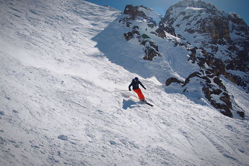 Low angle view of man skiing downhill on mountain