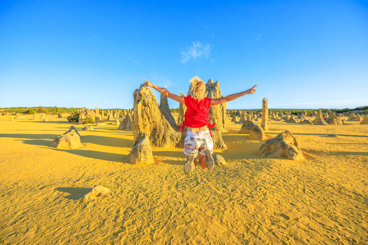 Rear view of woman with arms outstretched jumping against rock formation