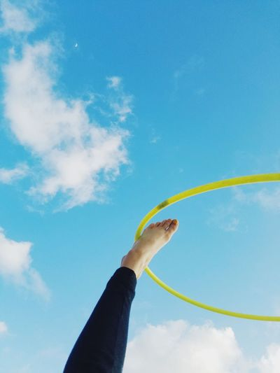 Low Angle View Of Woman With Hula Hoop Against Blue Sky