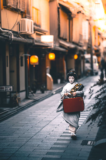 Through the streets of Kyoto. Geisha Japan Japan Photography Japanese Culture The Street Photographer - 2018 EyeEm Awards Beautiful Woman Building Exterior Built Structure Casual Clothing City Focus On Foreground Full Length Hairstyle Leisure Activity Looking At Camera One Person Outdoors Portrait Real People Street Streetphotography Week On Eyeem Women Young Adult Young Women The Traveler - 2018 EyeEm Awards
