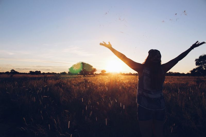 Rear view silhouette woman with arms outstretched standing on field during sunset