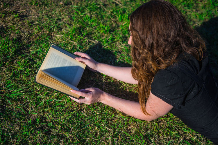 Young woman reading a book while lying down in the grass. One Person Nature White Woman Young Adult Portrait Curly Hair Freckles Black Dress Caucasian Candid Real People Smart Intelligent Intelligence Lifestyle Reading Green Outdoors Tranquility Sunny Day Beautiful Book Leisure Activity Lifestyles Day Women Adult Hairstyle Holding Grass Activity Studying Learning