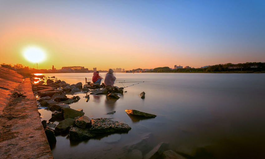Two fishermen fishing at sunset moment Adult EyeEmNewHere Fisherman Fishing Long Exposure Nature Outdoors People River Riverbank Silhouette Sky Sunset Vacations Water