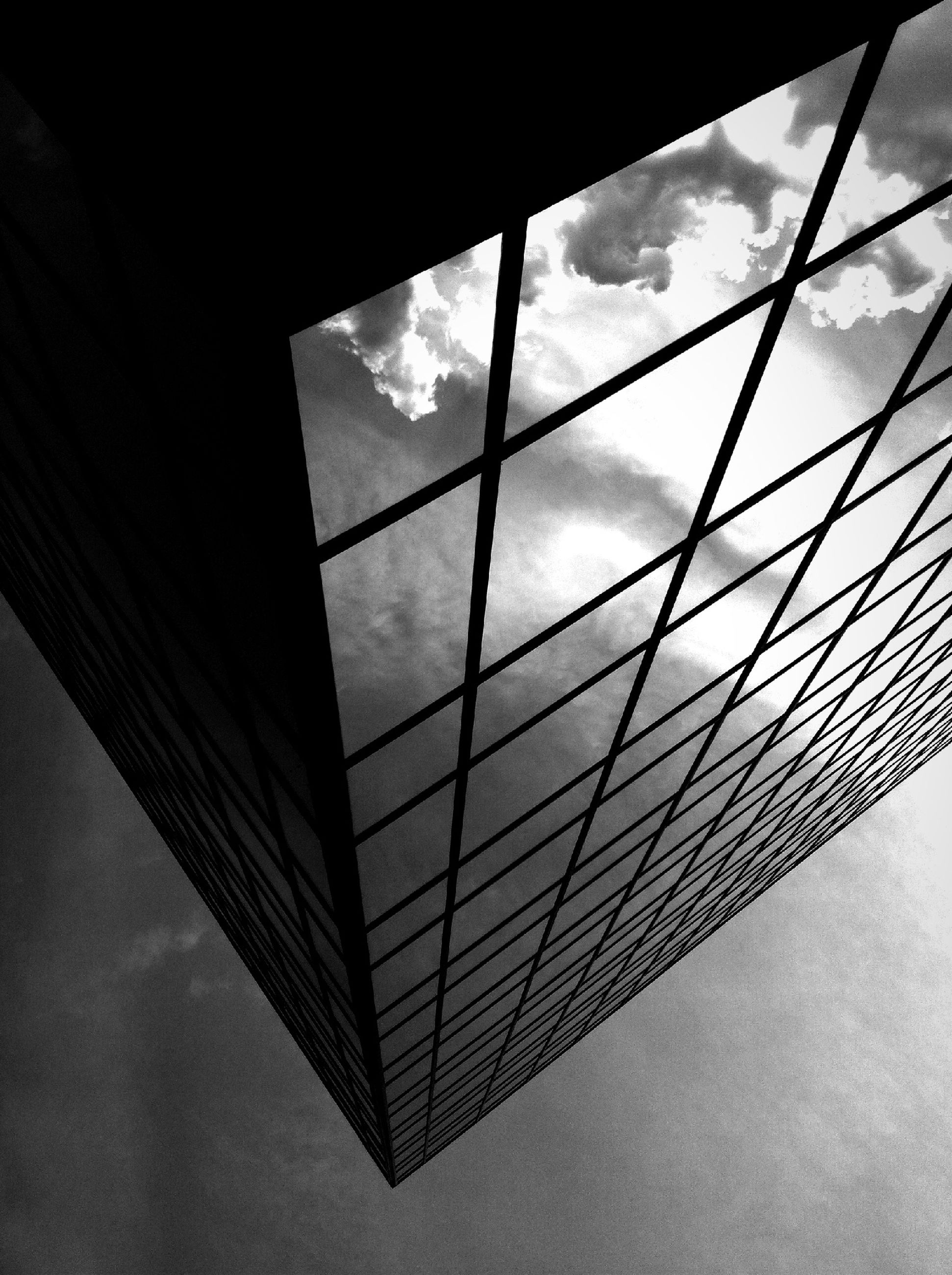 low angle view, architecture, built structure, sky, modern, glass - material, indoors, pattern, reflection, cloud - sky, directly below, day, geometric shape, cloud, architectural feature, window, building exterior, design, shape, no people