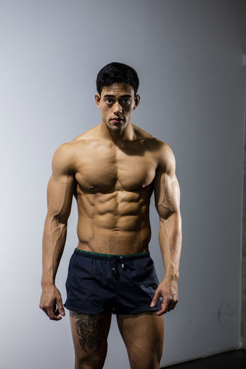 Muscular male fitness model posing behind a grey wall looking directly at the camera. Adult Asian  Athlete Body & Fitness Human Body In Shape Long Shot Looking At Camera Man Nam Vo Shirtless Sportsman Fitness Model Grey Wall Handsome Hunk Male Muscle Muscular Build One Person Shorts Strong Studio Shot Tatoo Torso