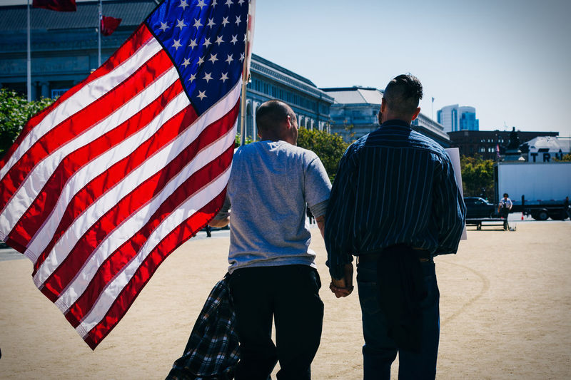 Rear View Of Gay Couple Holding Hands And Walking With American Flag