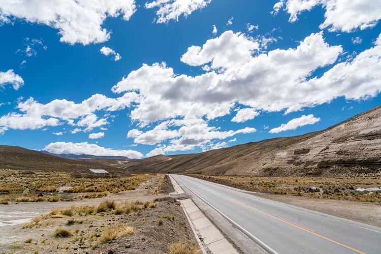 Empty road on desert against sky
