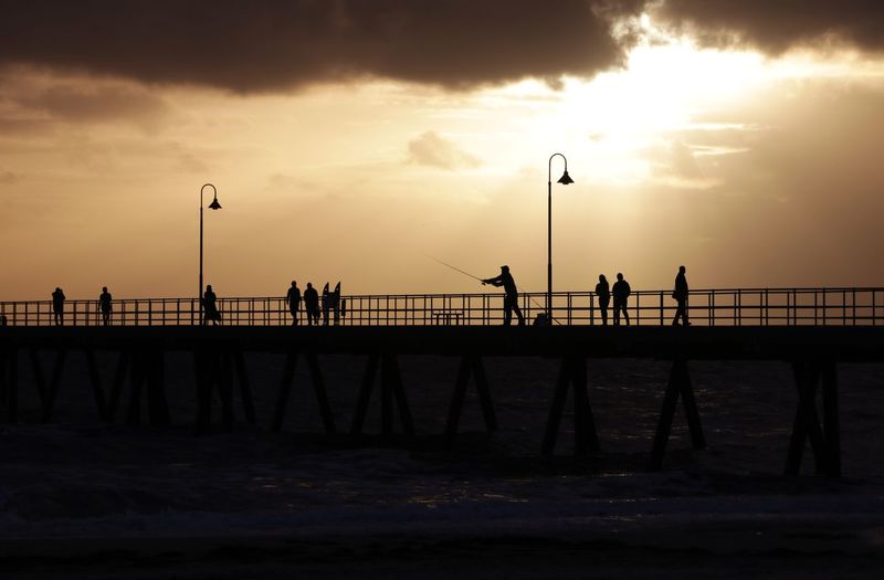 Silhouette people on pier against sky during sunset