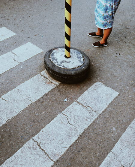 Low Section Of Woman Standing By Pole On Street