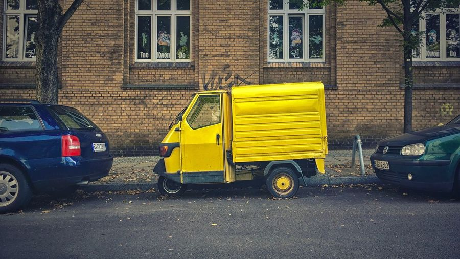3 Wheeler Audi Berlin Building Exterior Car City Life Graffiti Italian Italy Land Vehicle Mode Of Transport Parked Parking Road Side View Street Transportation Tree Vibrant Color Volkswagen Wall Wall - Building Feature Windows Yellow Yellow Color