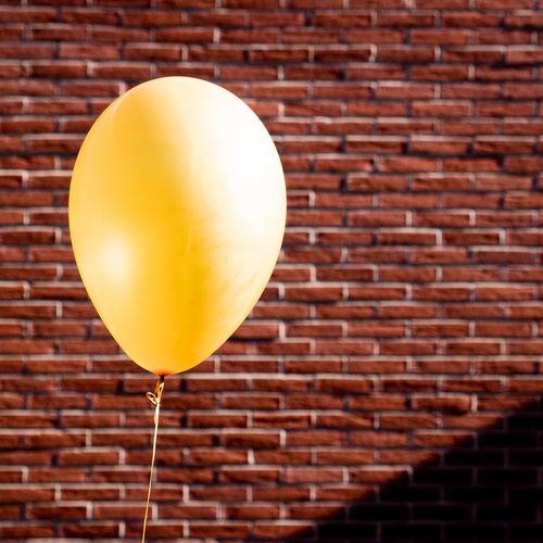 Close-Up Of Yellow Balloon Against Brick Wall