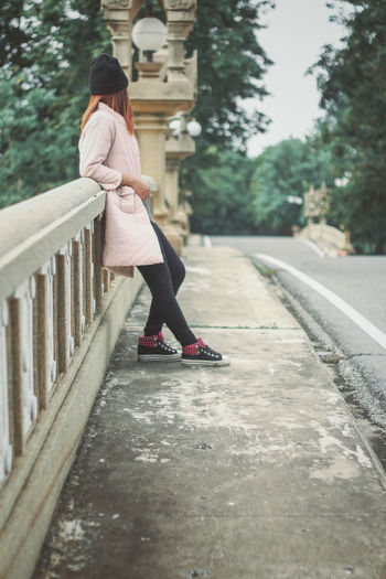 Woman standing by railing in city